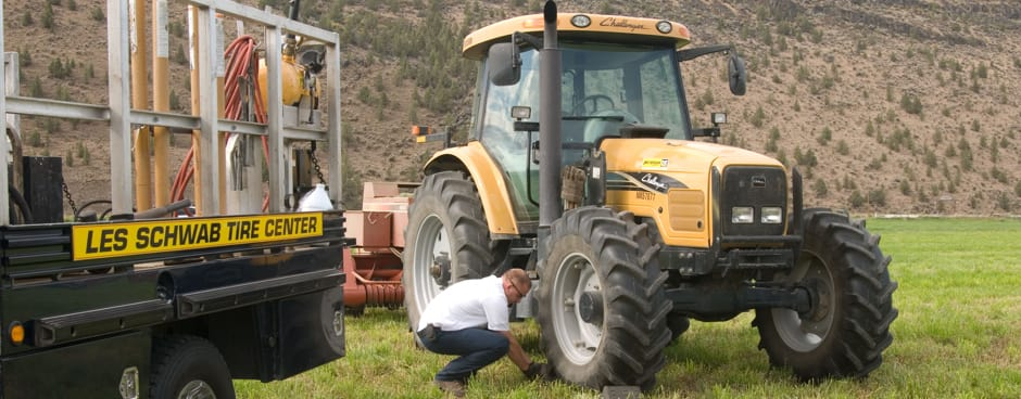 A Les Schwab technician repairing a tractor tire out at someon's farm.