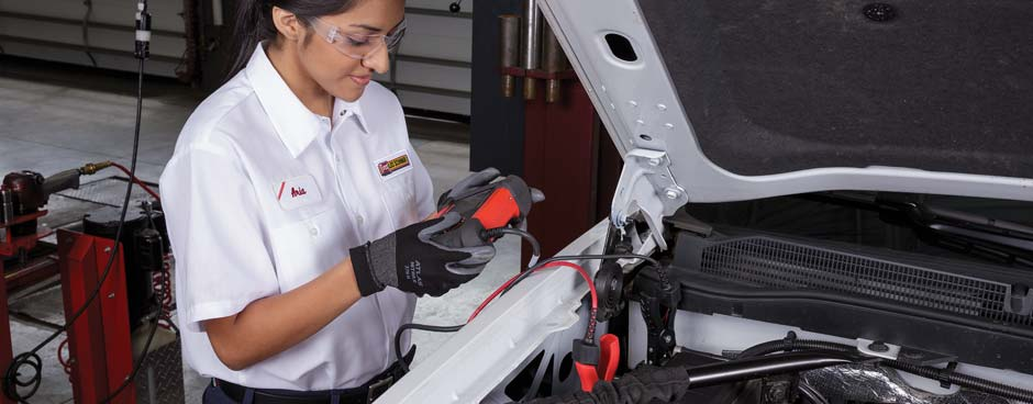 Female employee performing a battery test on a white pickup.