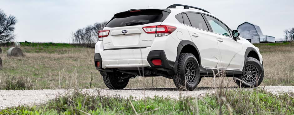 White CUV with overlanding kit installed.