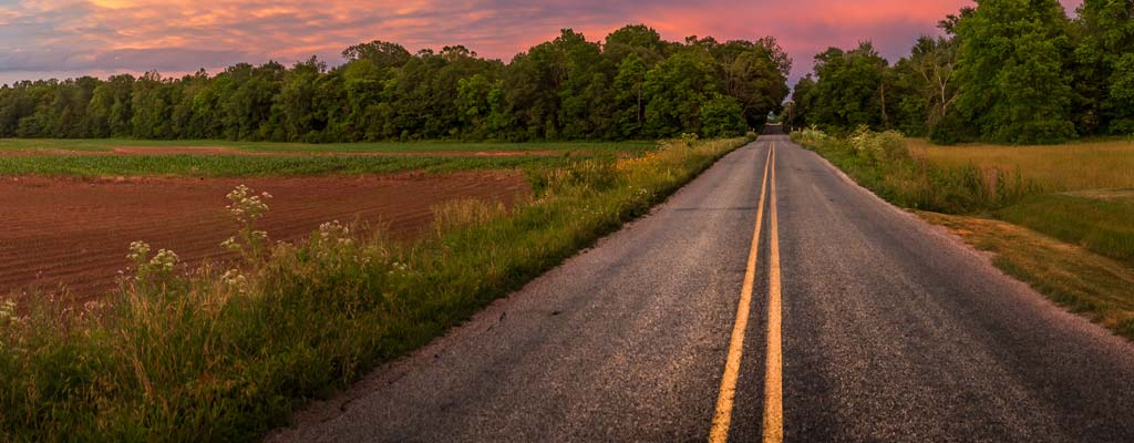 A two-lane road stretches forward past farmlands on a colorful spring day.