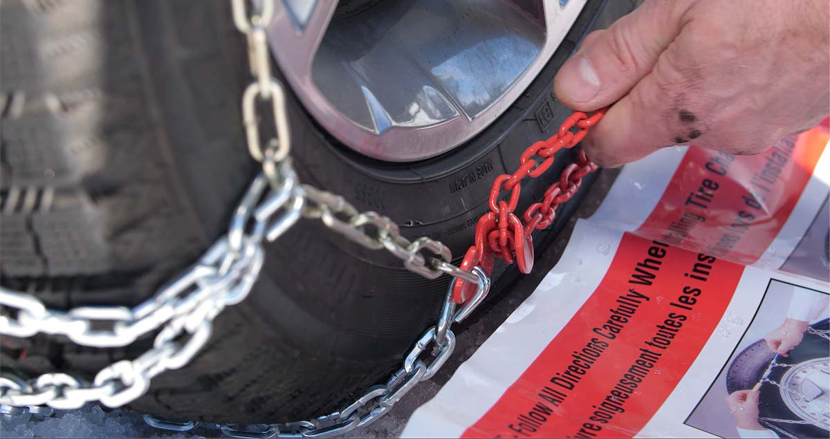 Pulling a long red chain through the chain guide on tire chains.