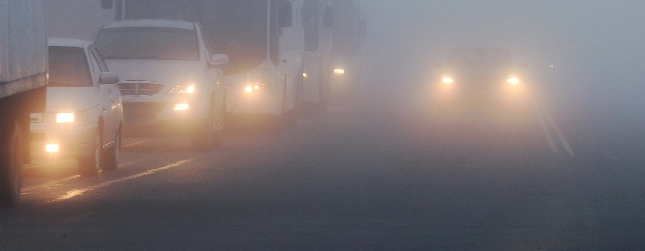 Vehicles on a foggy highway.
