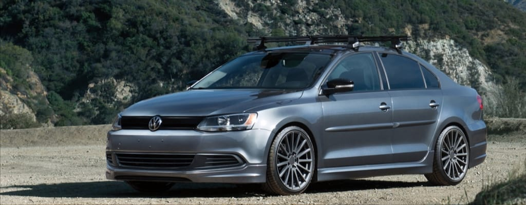 A platinum gray Volkswagen seden with a rooftop bike rack parked on a dirt road out in the country.