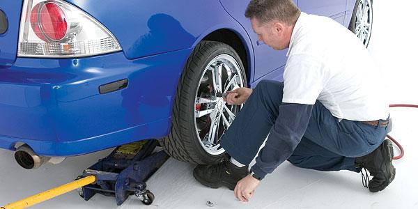 Tire technician installing wheel lug nuts
