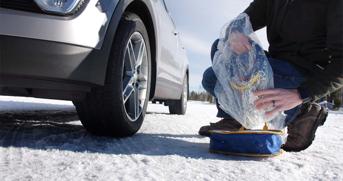 Man removing tire chains from the storage case.