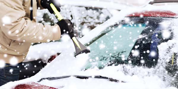 A man scraping ice from his car window.