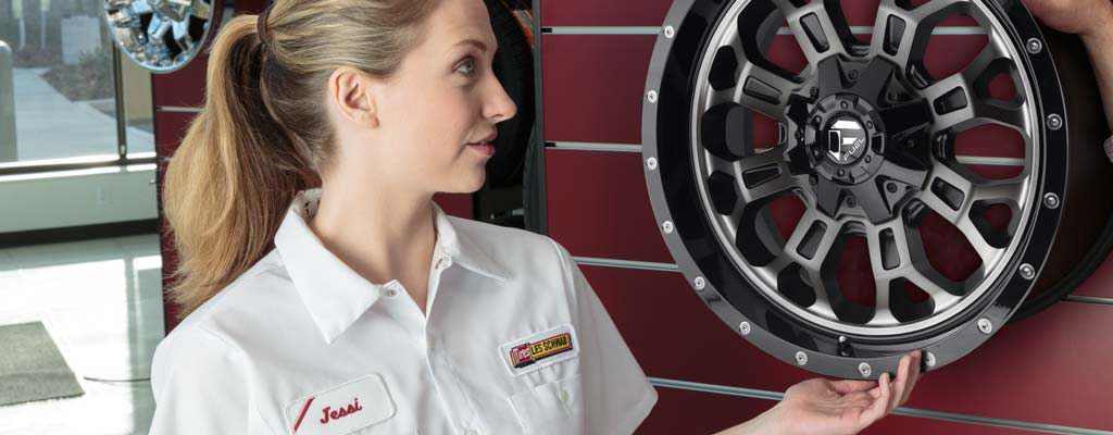 A Les Schwab technician inspects a tire being carted in by another Les Schwab technician.
