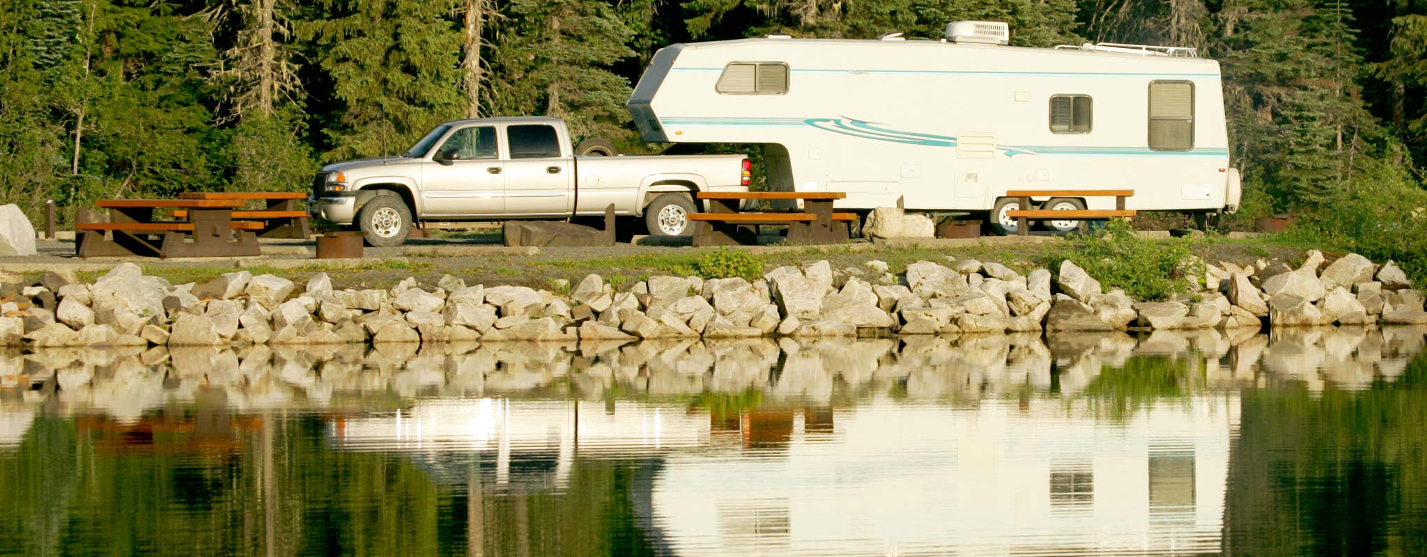 A pickup with a fifth wheel travel trailer parked in a campground next to a lake.