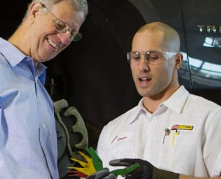 A Les Schwab technician uses a color-coded brake gauge to explain upcoming brake service to a customer
