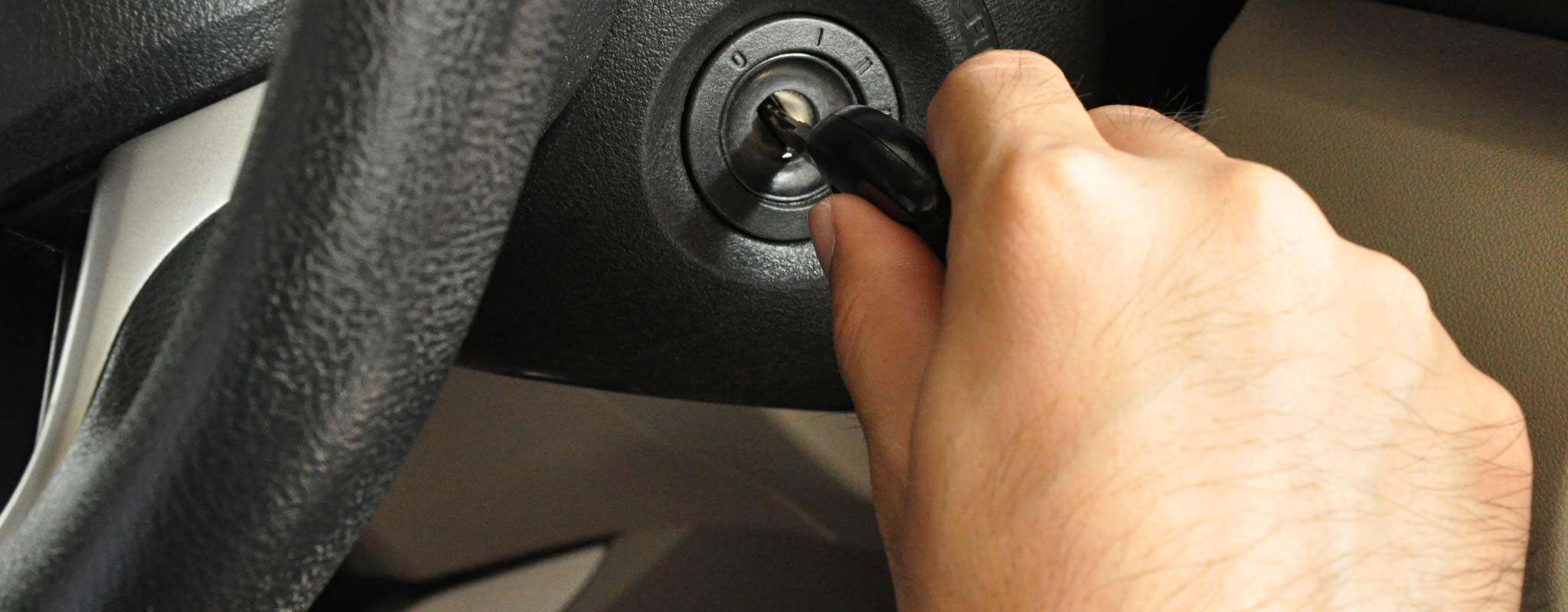 A hand putting a key in a car ignition.