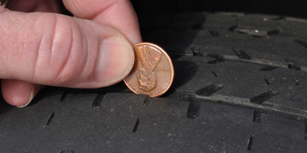 A person checking their tire tread deapth with a penny.