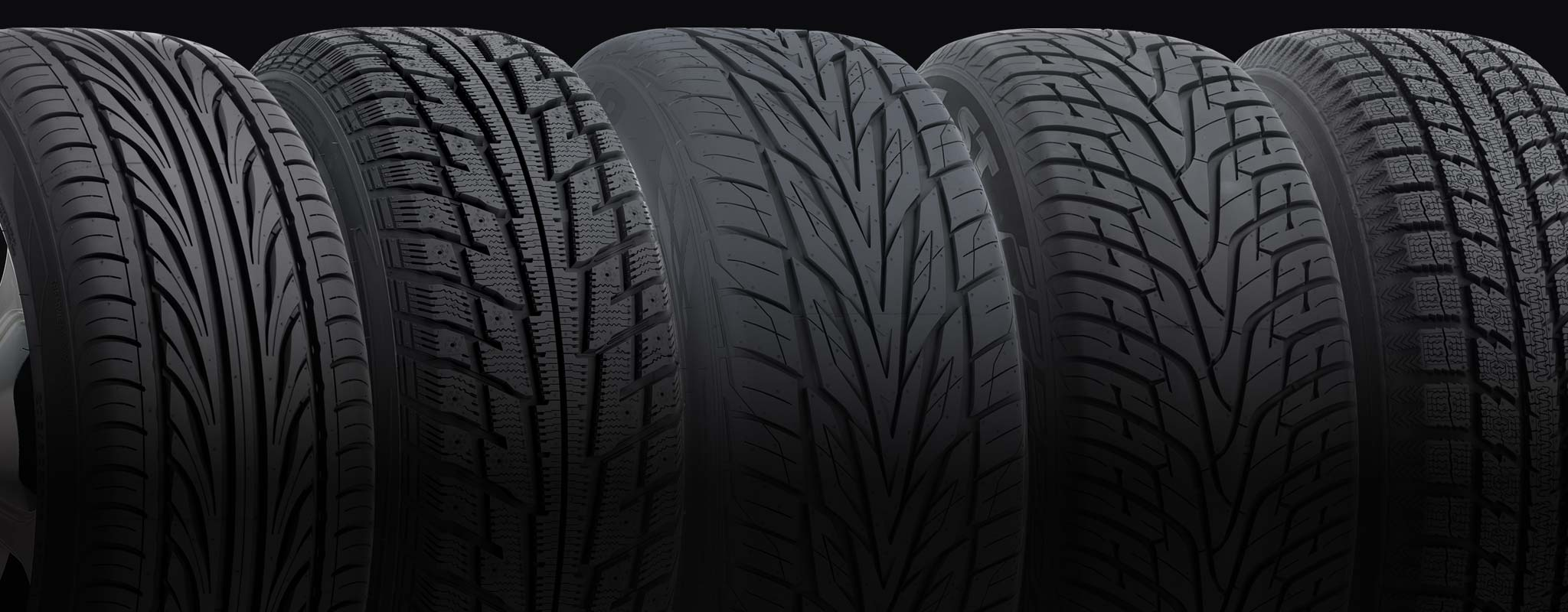 A set of directional tires with different tread designs lined up.