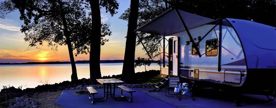 Travel trailer next to a lake at sunset.