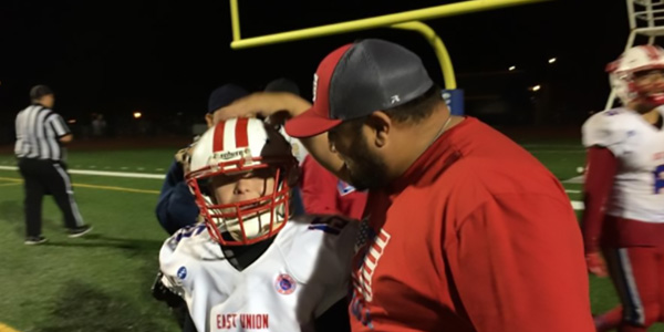 The East Union high school football coach pats a player on their head.