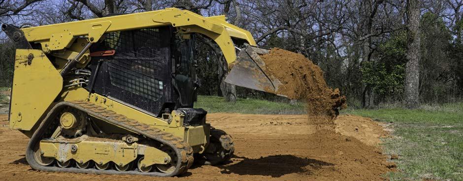Skid steer moving dirt in it's loader