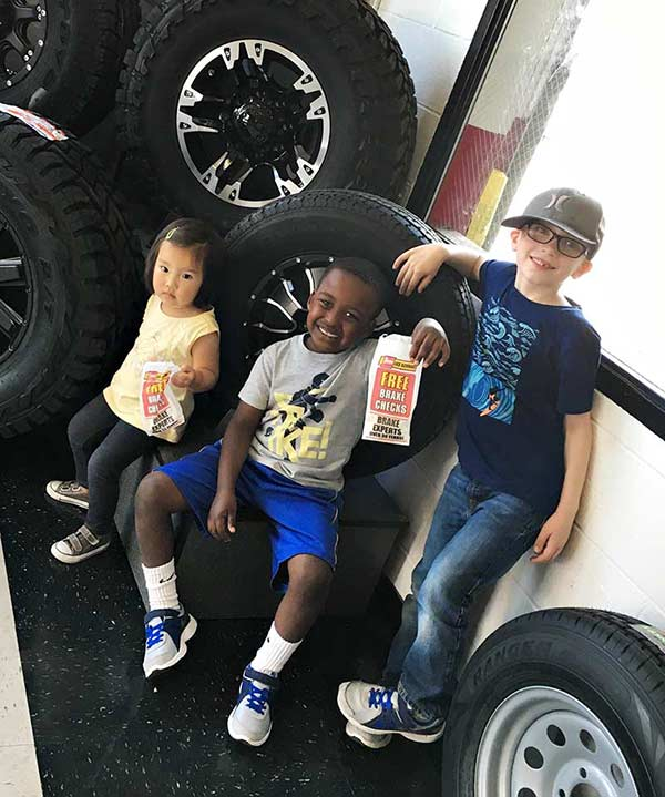 Kids enjoying popcorn at a Les Schwab Tire Center.