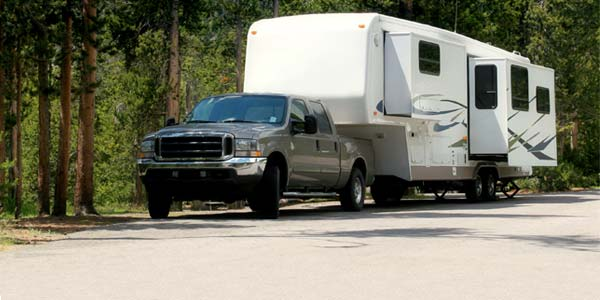 A truck and travel trailer parked in a forested campground.