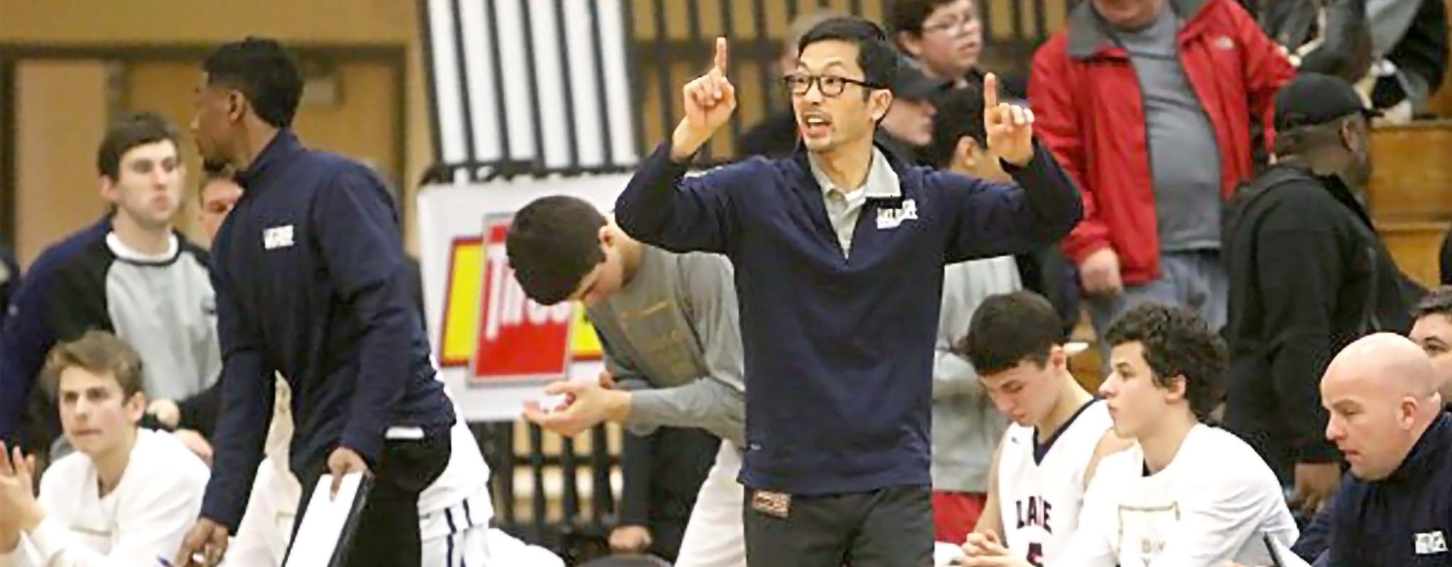 Lake Oswego basketball coach, Marshall Cho, courtside during a game.