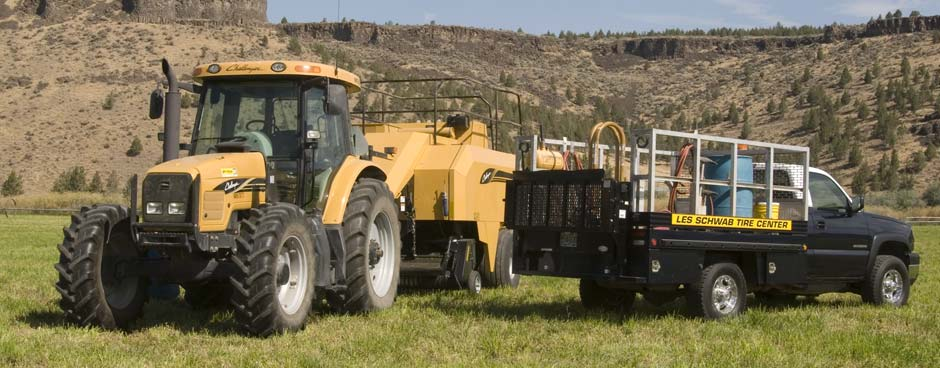 Les Schwab service truck in a field with a yellow tractor