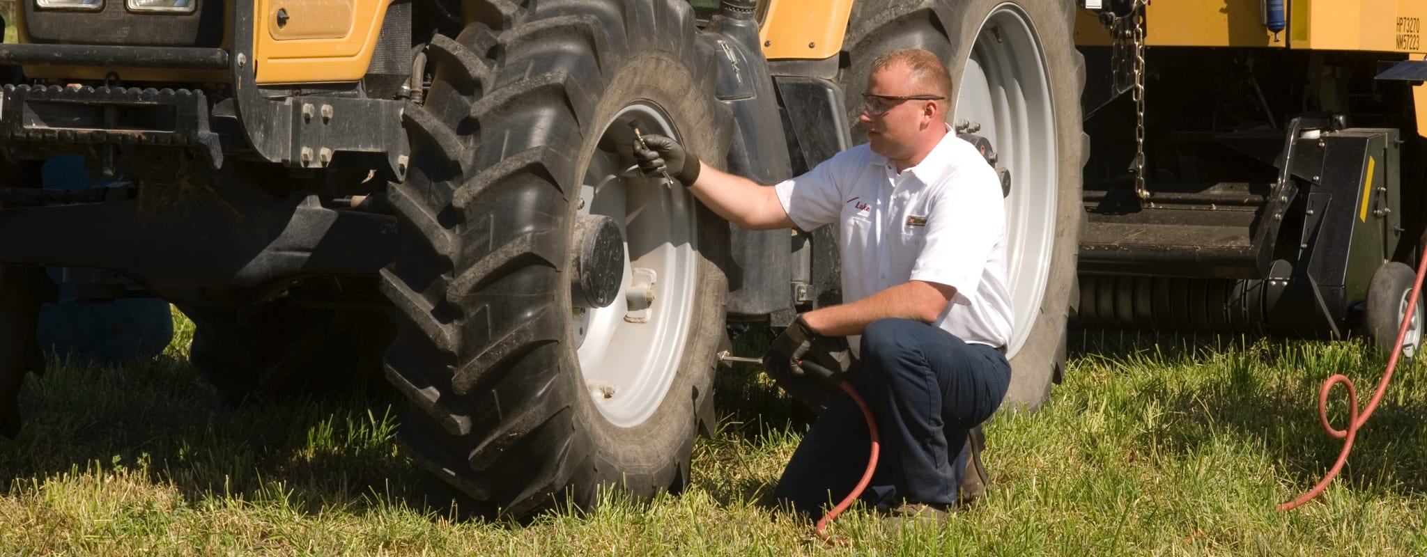 A Les Schwab technician checks the air pressure of a tractor tire.
