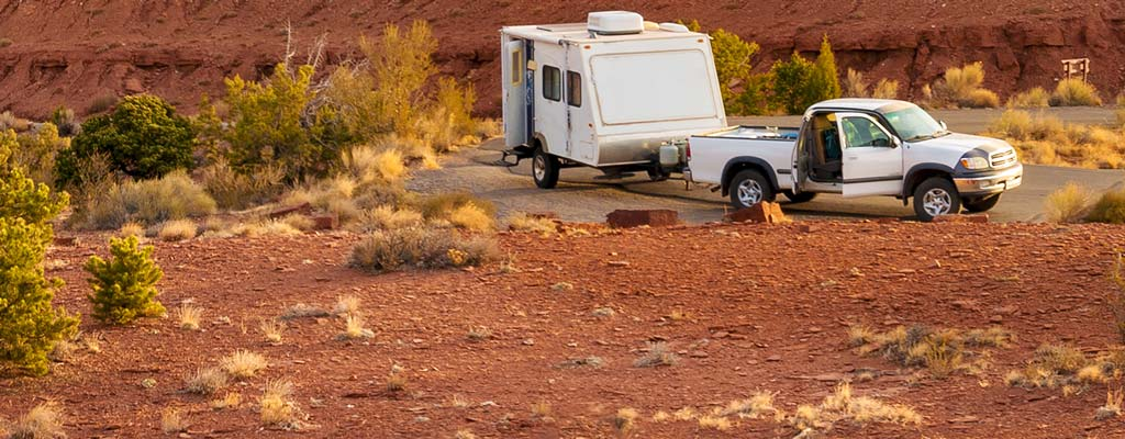 Pickup and camp trailer parked roadside in a Utah National park.