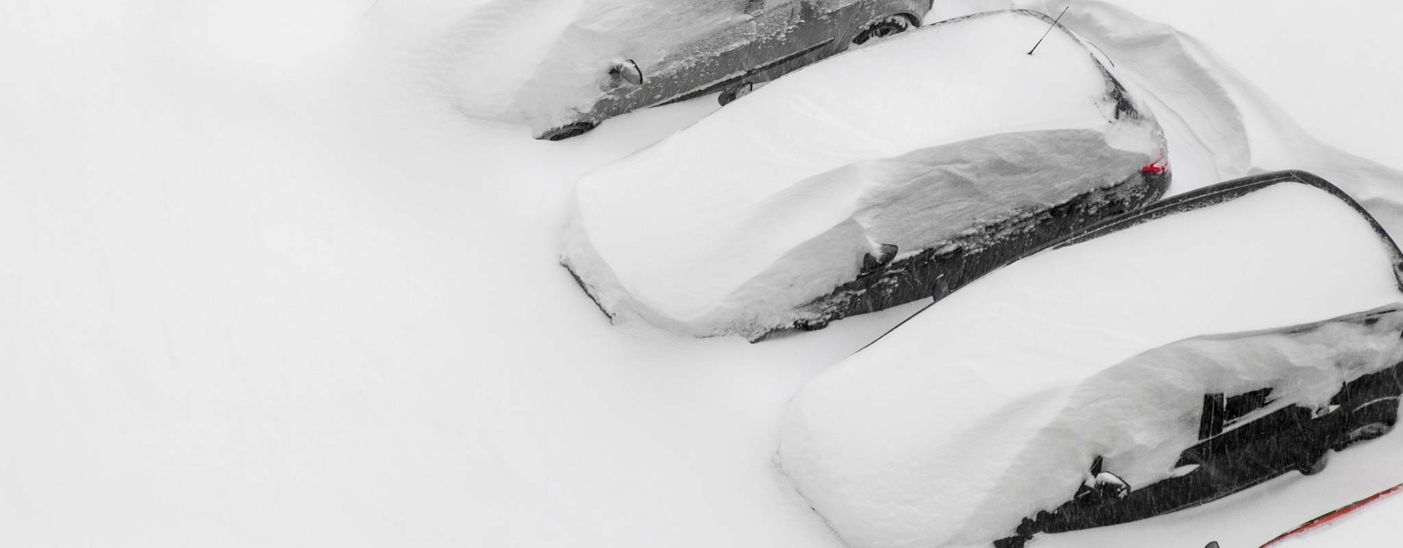 Cars buried under a large snowfall.