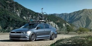 A photo of a car with bicycle on the roof while driving through the mountain roads