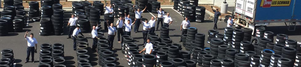 Amidst stacks of new tires, Les Schwab employees wave hi from the parking lot of the Norco location.