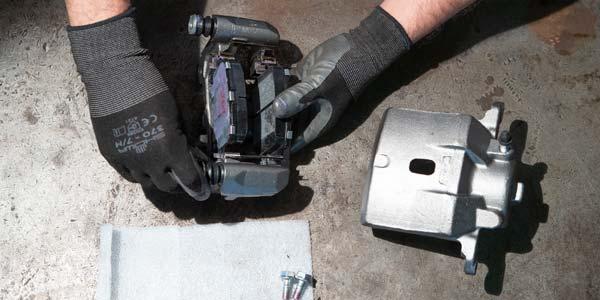 A Les Schwab technician adding new brake pads to a remanufactured brake caliper.