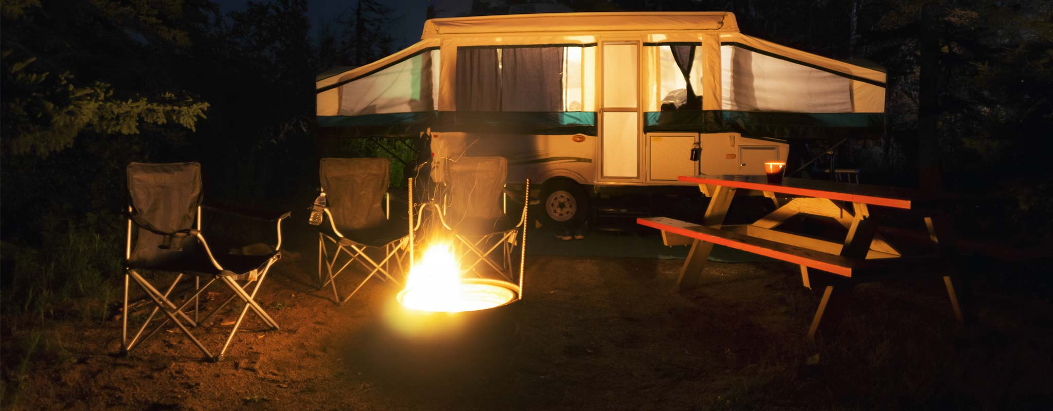 A pop-up tent trailer with it's lights on next to a campfire.