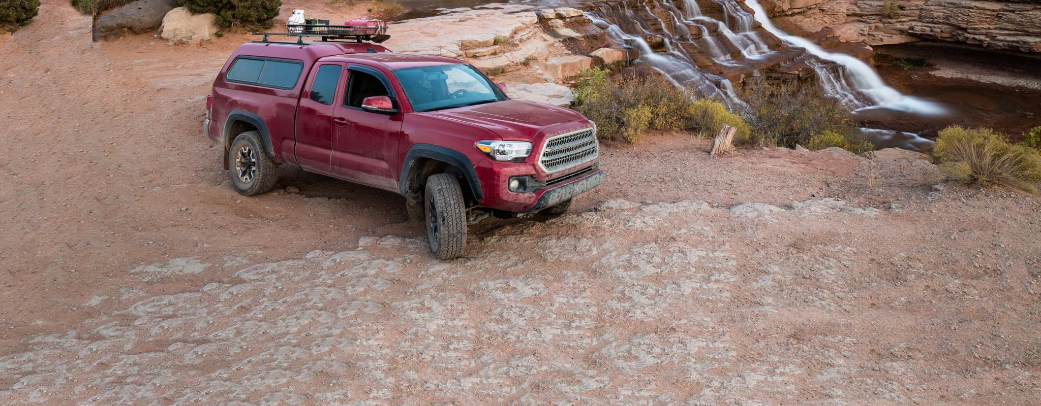 Red pickup with canopy on sandy ground near a waterfall.