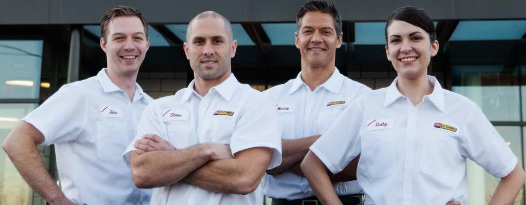 Four Les Schwab technicans pose inside a garage.