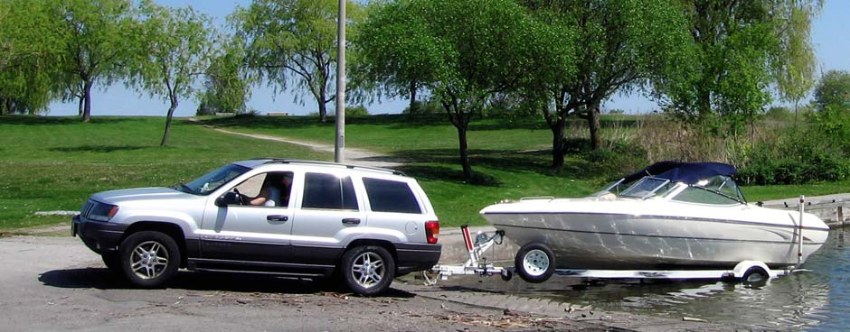 A Jeep Cherokee pulls a boat out of the water on a trailer.