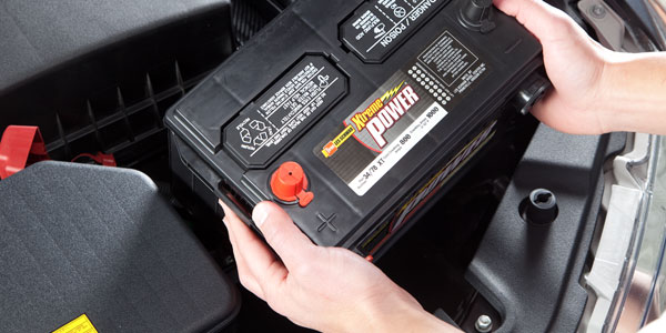 A close up of a technician installing a new car battery.