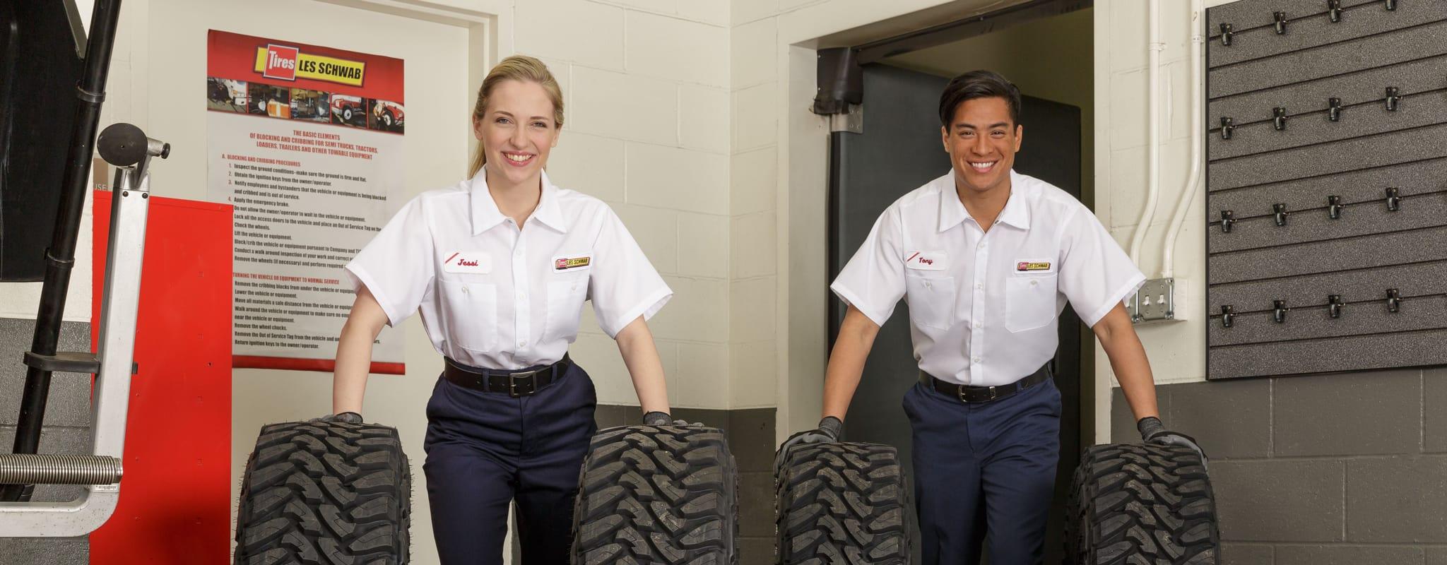 Two Les Schwab technicians rolling a set of truck tires across the floor.