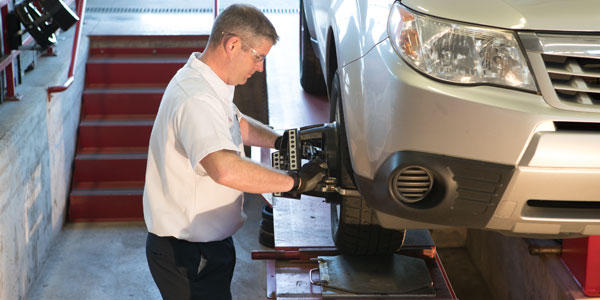 A Les Schwab technician performing an alignment on a car.