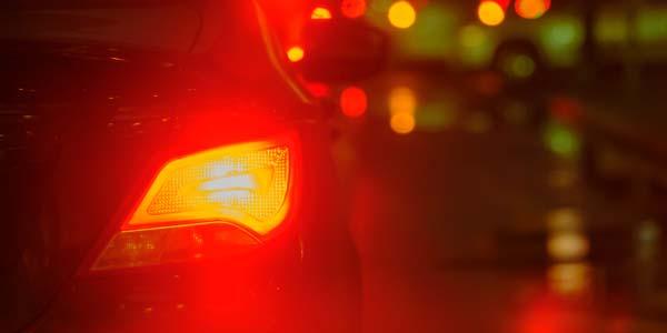 Illuminated car brake light at night.