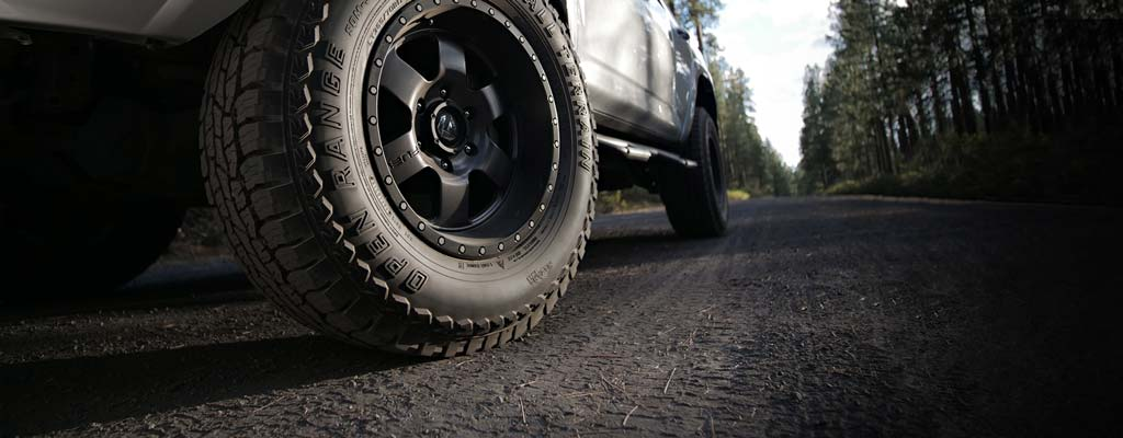 Closeup of a vehicle tire on a gravel forest road.