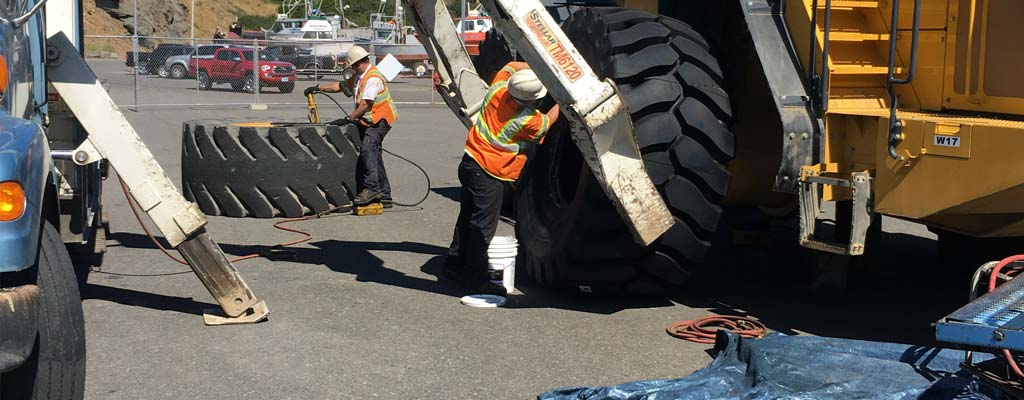 Les Schwab employees changing a giant tire.