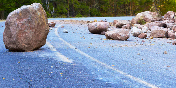 A rock slide with large boulders in the middle of a road.