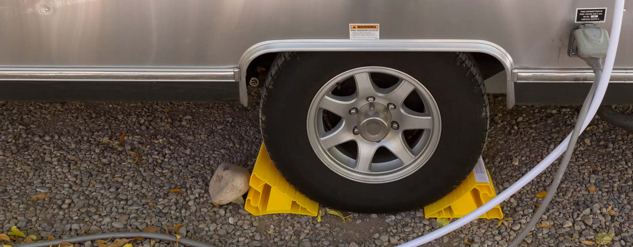 An tire with tire blocks on an aluminum sided RV.