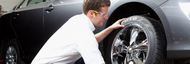A Les Schwab technician mounts a new tire onto a vehicle.