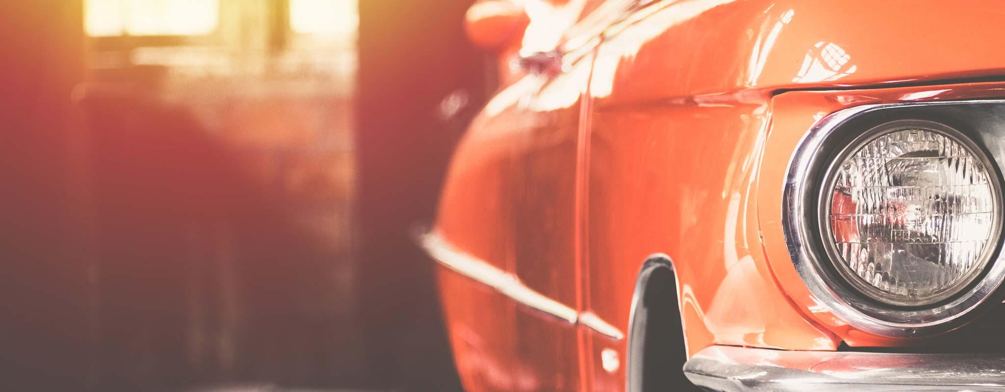 A red classic car in a garage.