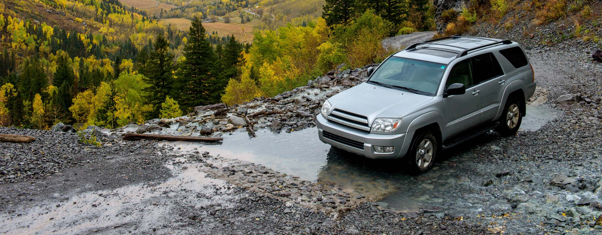 SUV driving on wet gravel road.
