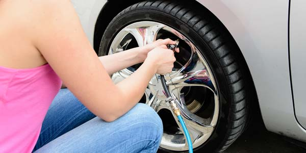 A woman checking the air pressure in her car tire.