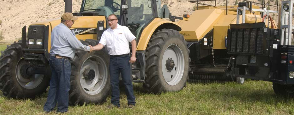 Les Schwab employee and farmer shaking hands next to a tractor