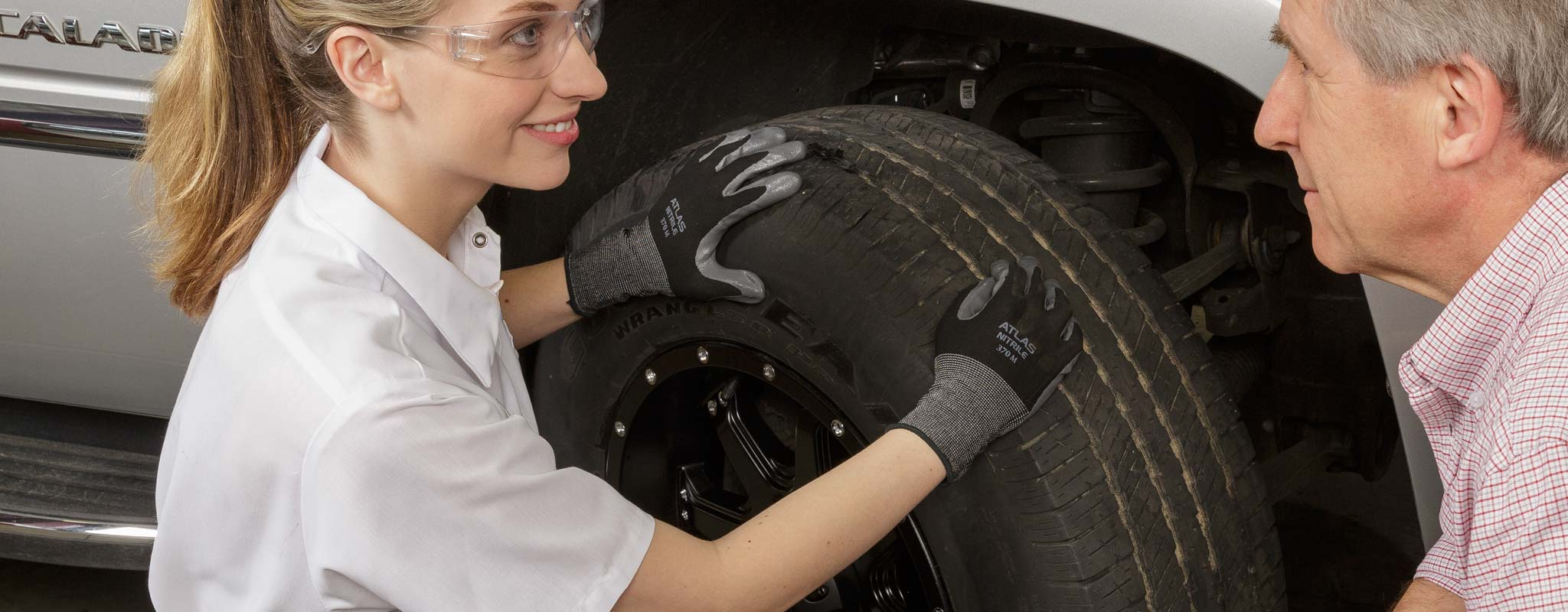 Female tire technician talking to a customer about his tire.