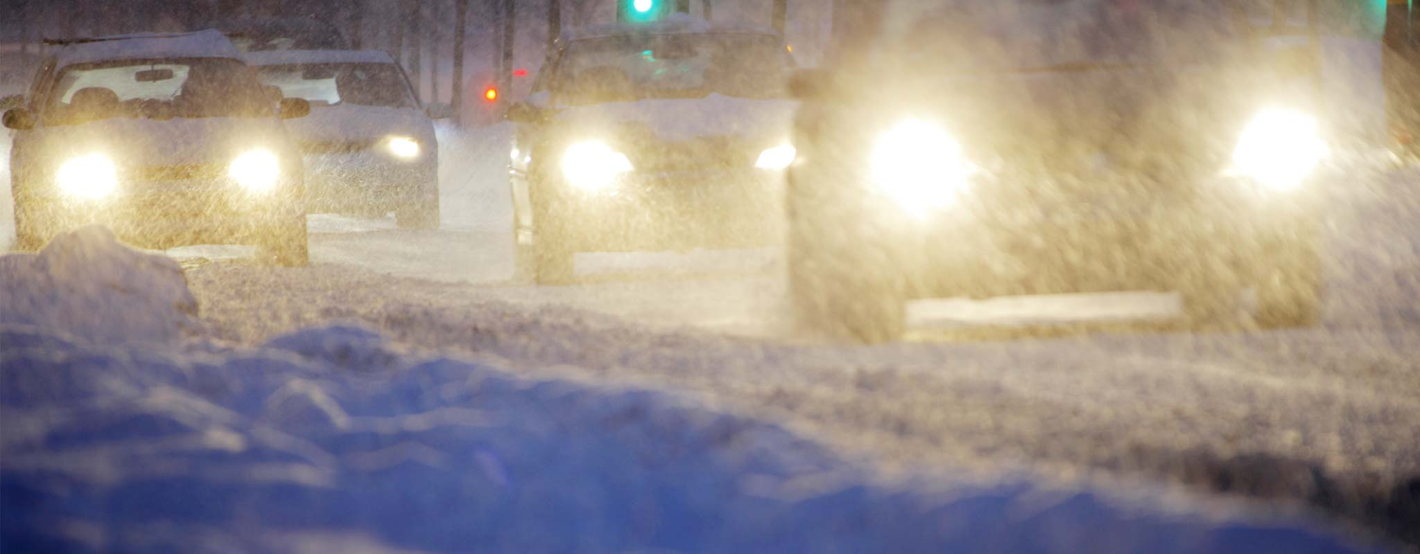 Headlights shining on a snowy winter road.