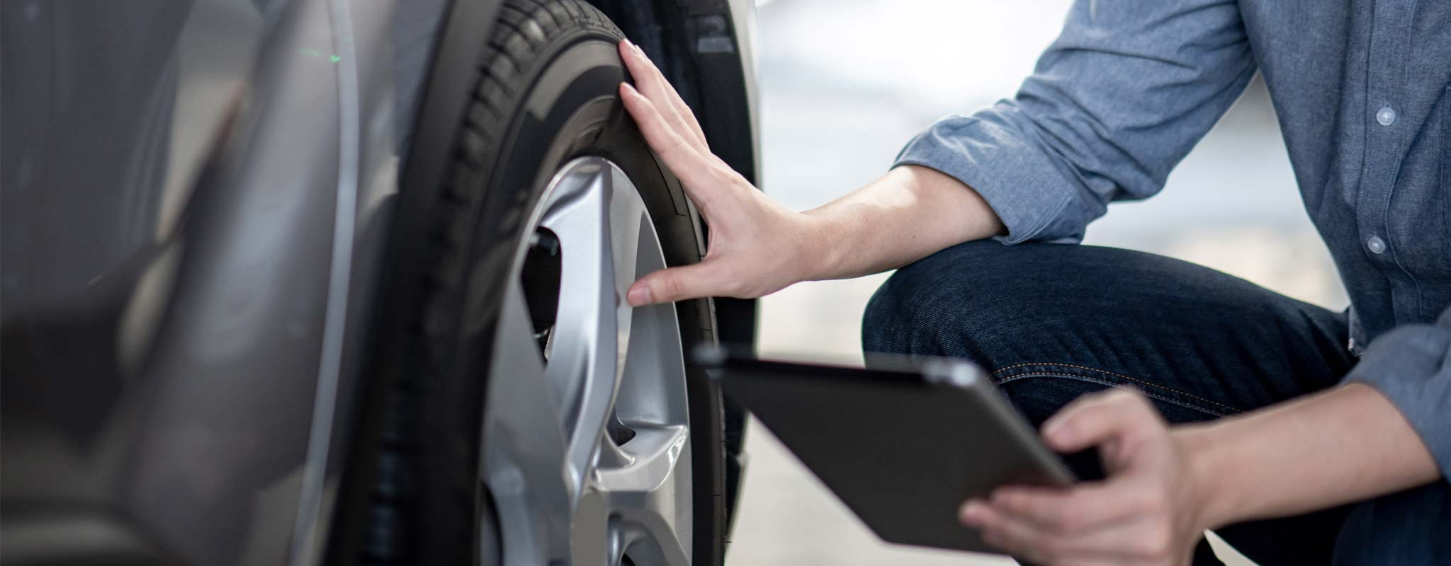 Person checking his tire with a tablet in his hand