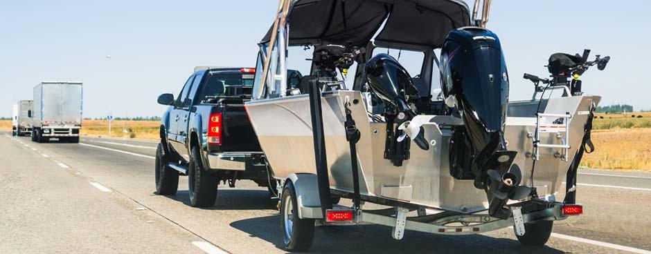Black pickup pulling an aluminum boat on freeway.